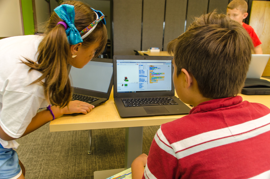 Children building a game on a laptop