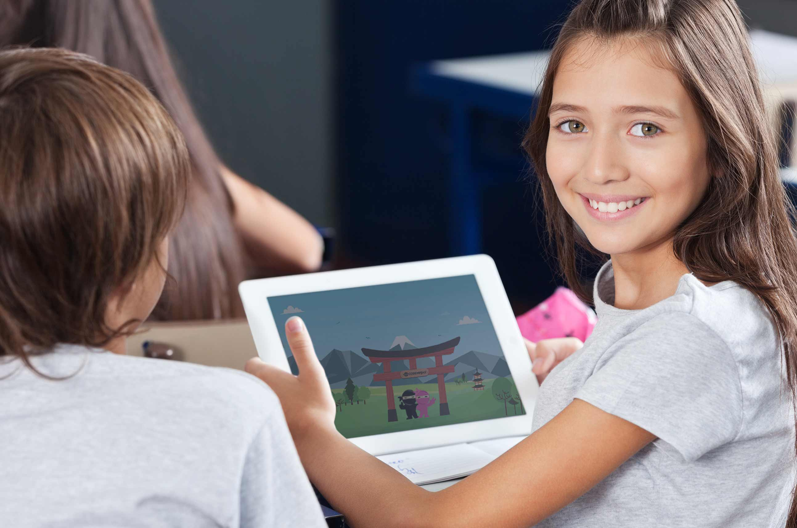 Girl smiling using a tablet